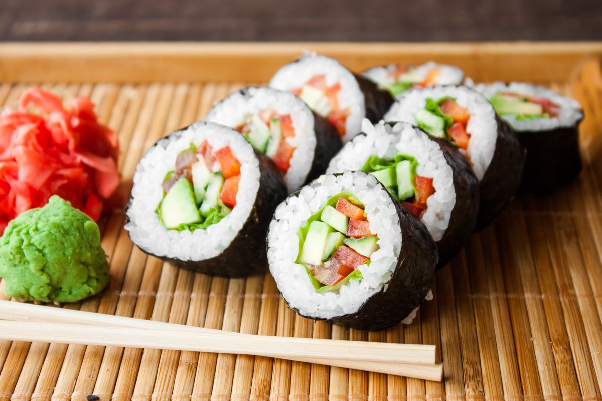 Vegan sushi roll stuffed with cucumber and tomato and wrapped in nori