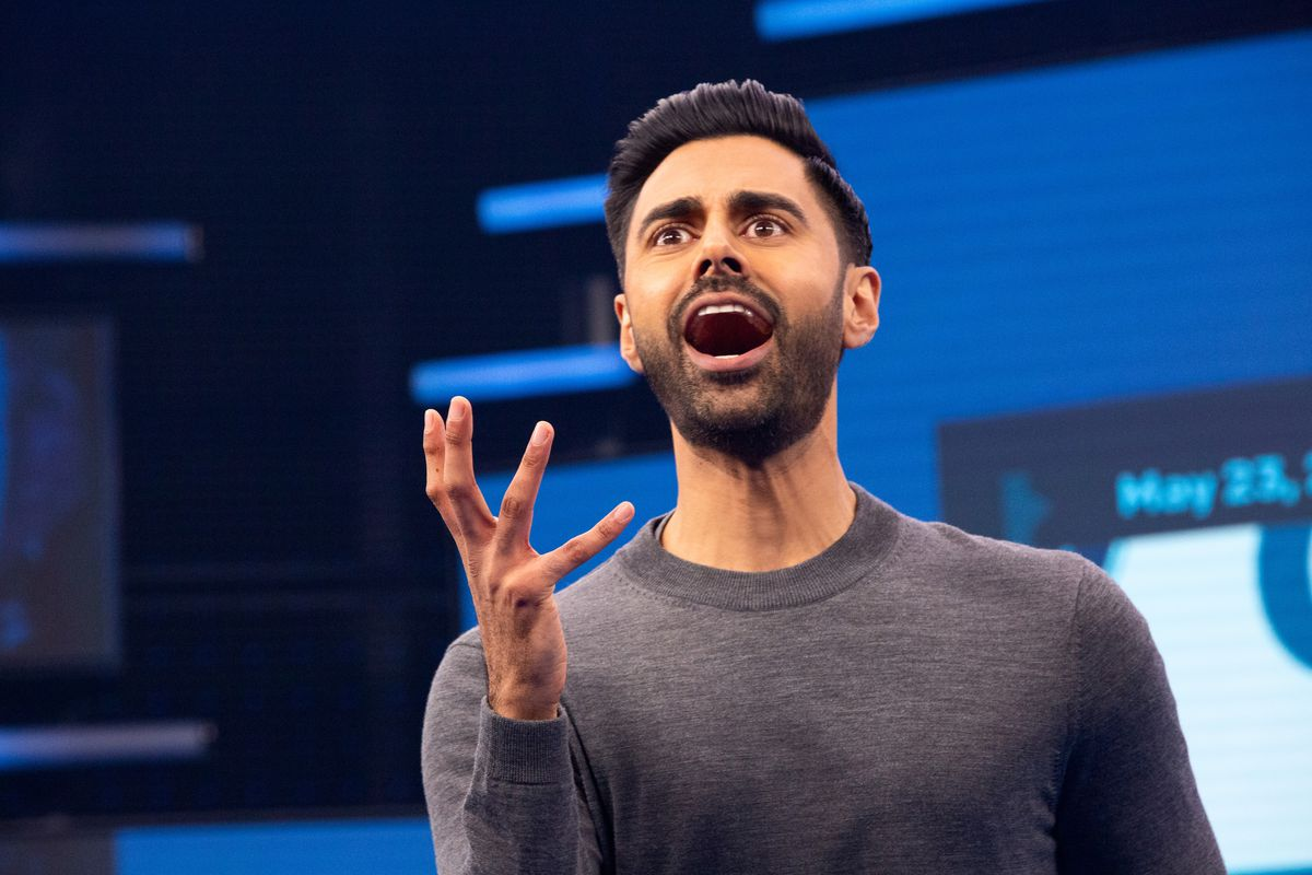 an Indian man in a gray sweater, Hasan Minhaj, holds up his hand on Patriot Act with Hasan Minhaj