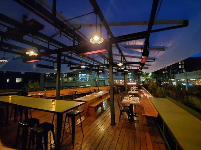 The covered rooftop patio at Capitol Hill restaurant Terra Plata with wooden communal tables and a surrounding garden