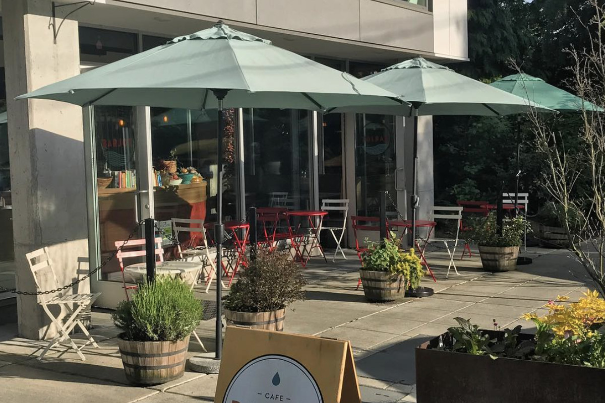 A patio on a sunny day with green umbrellas covering outside seating