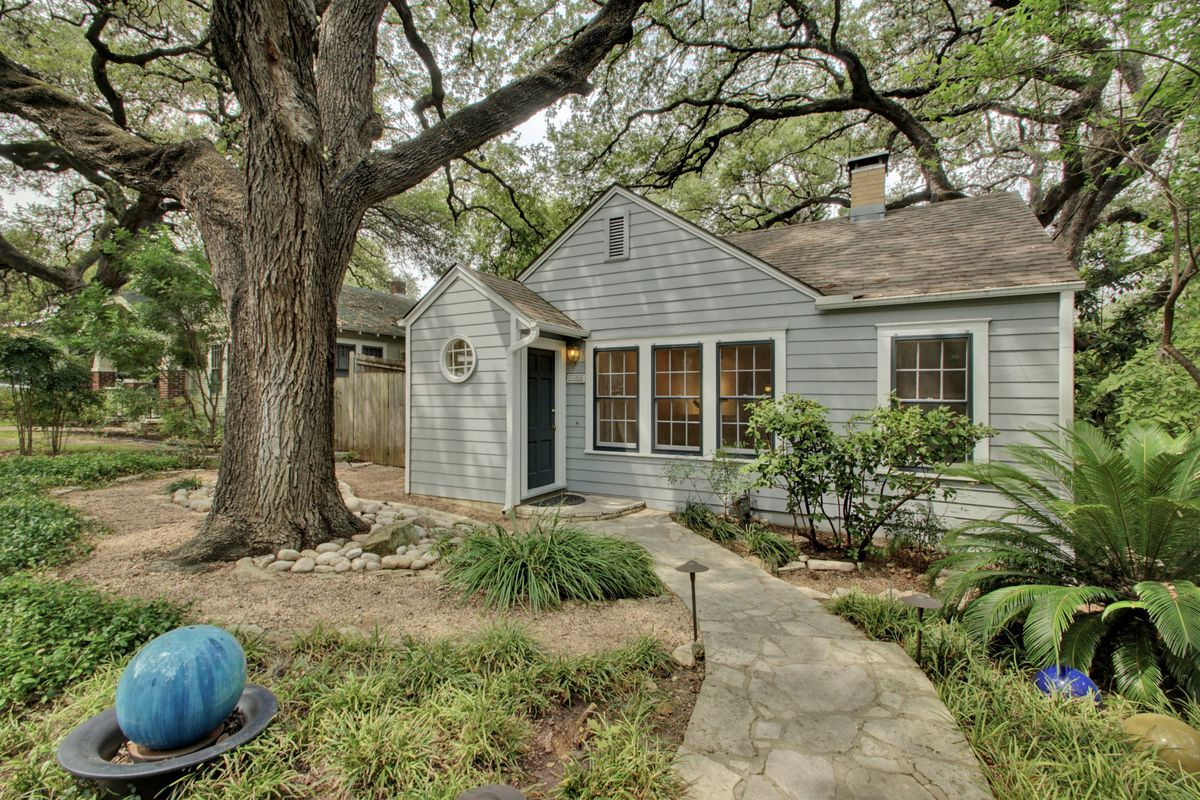 Photo of gray frame 1930s house with big oak in front