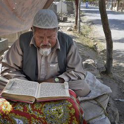 In this Thursday, Sept. 6, 2012 photo, Pakistani Gulbar Abbas reads the Quran at  the entrance of the Shiite Muslim graveyard in Pakistan's violent Baluchistan capital of Quetta, Pakistan, where radical Sunni Muslim rivals have terrorized and murdered minority Shiites in a wave of suicide bombings and target killings. In recent years Pakistan's sparsely populated southwestern Baluchistan province has been spiraling deeper into chaos, wracked by a secessionist insurgency that has been overtaken in the last two years by a violent sectarian campaign.