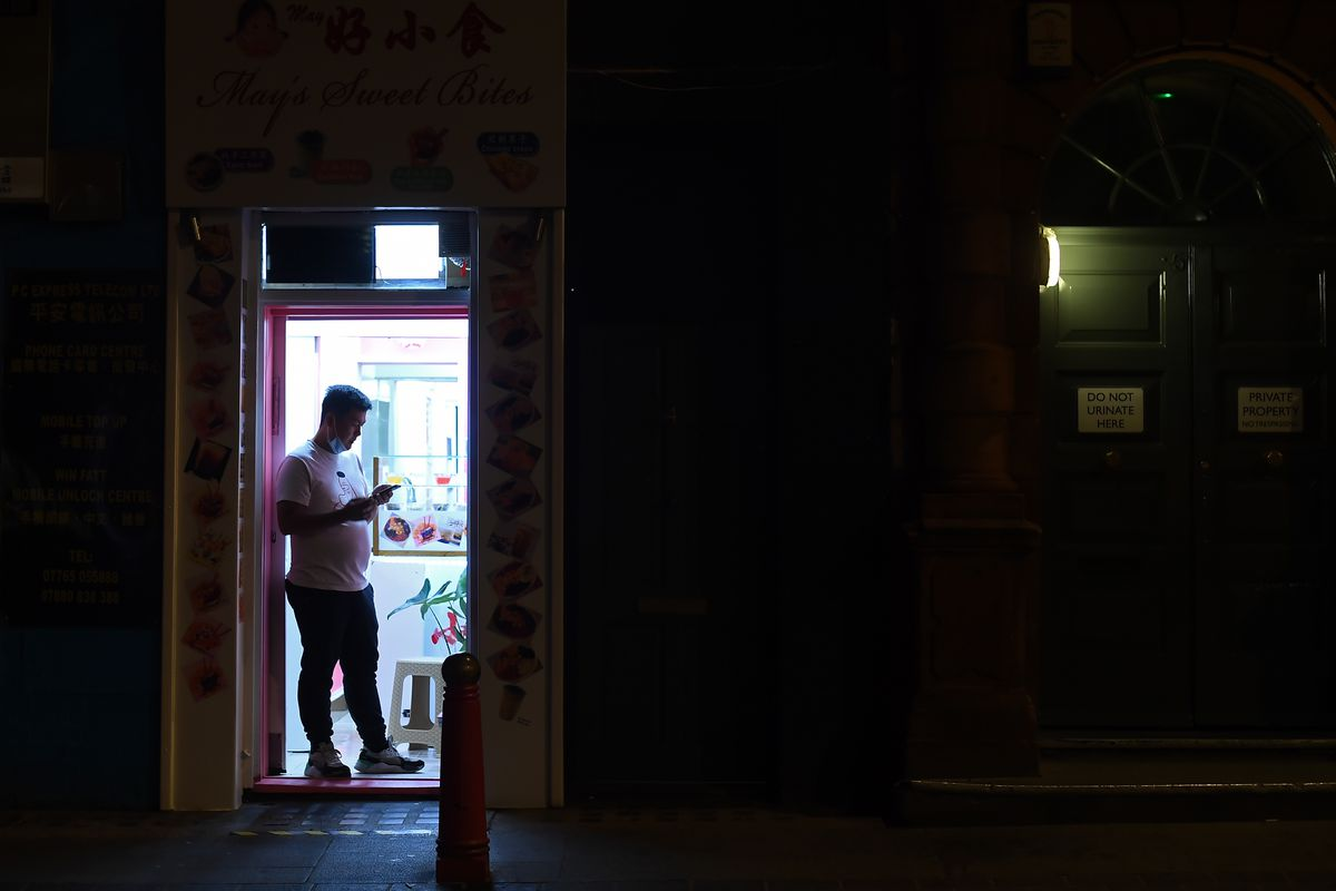 A man stands in silhouette in a brightly lit doorway in Soho — the rest of the image is dark