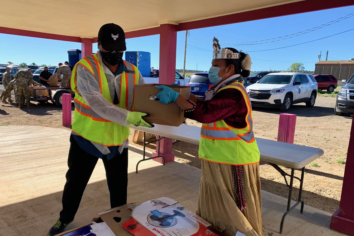 Navajo Nation President Jonathan Nez hands a box to a health care worker in an outdoor testing facility in Arizona.