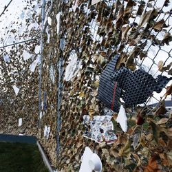 Debris and leaves are pushed against a baseball backstop by the wind in Farmington, Thursday, Dec. 1, 2011.