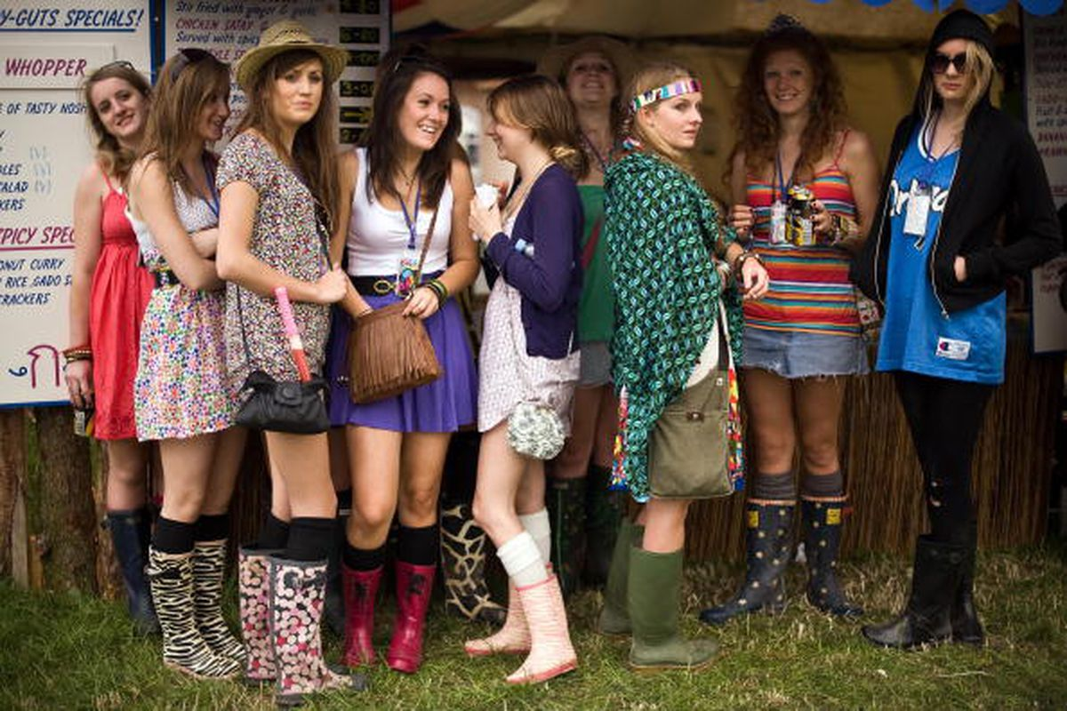 These girls, trying to stay dry at a U.K. concert, forgot their raincoats. Don't be them. Image via Getty