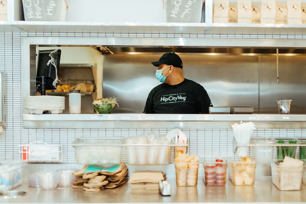 a counter at hipcityveg with a restaurant worker behind the counter in the kitchen