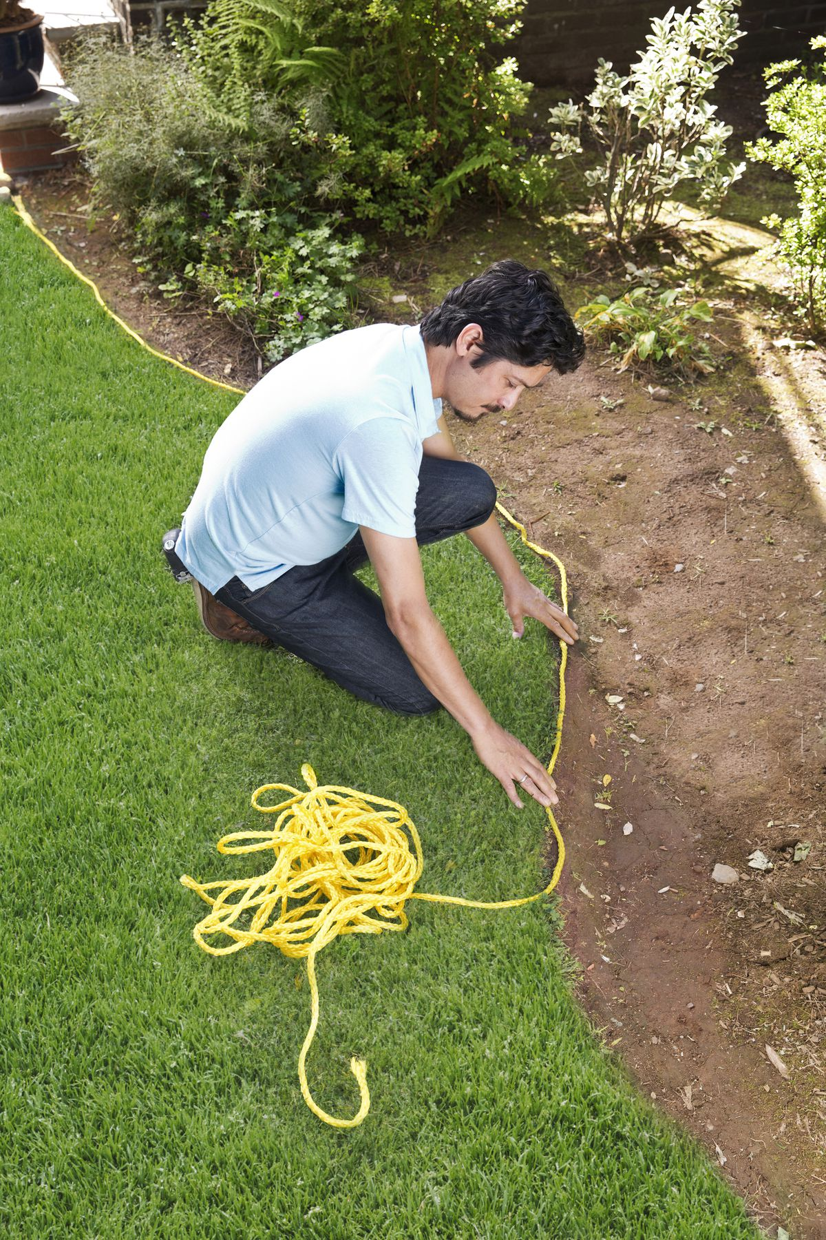 Man Lays Length Of Rope Along Edge Of Garden Bed