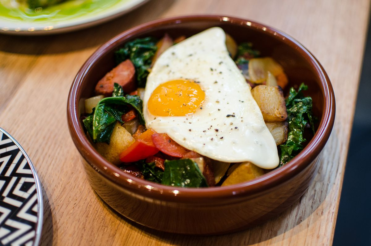 A sunny-side-up egg sits over kale and linguica in a brown dish.