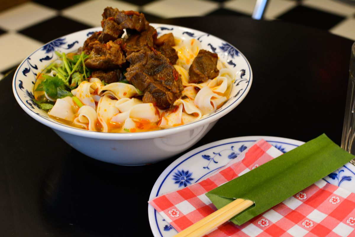 A bowl of beef noodles, next to a plate with chopsticks.