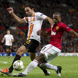 Manchester United's Patrice Evra, right, fights for the ball against  Galatasaray's Selcuk Inan during their Champions Graoup H soccer match at Old Trafford Stadium, Manchester, England, Wednesday, Sept. 19, 2012.