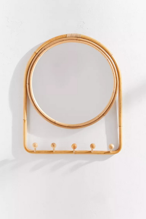 Round rattan mirror with small hooks on the bottom frame.