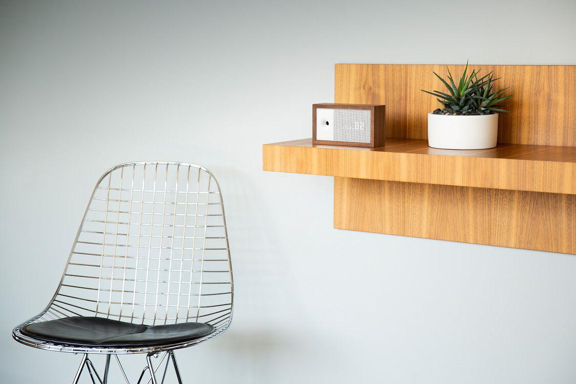 A small air quality monitor that looks like a retro radio sits on a wood shelf with a succulent and a stylish wire chair nearby.