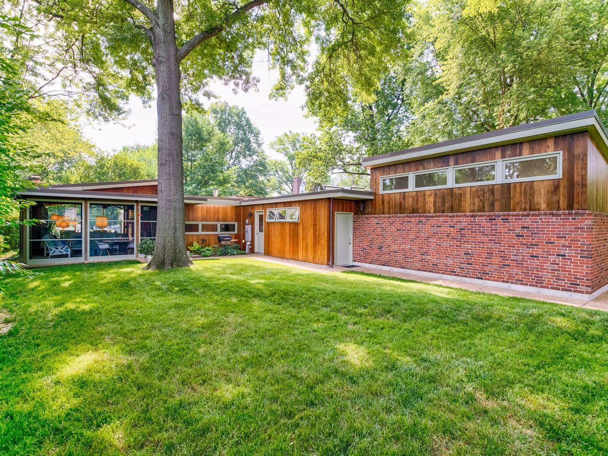 An exterior view of a midcentury house with brick and wood and a green lawn.
