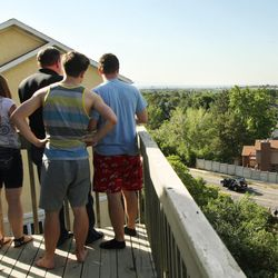 Erick Mosteller and his kids Hallie, Erick and Andrew watch from their back balcony as Sandy police investigate a deadly shooting on Tuesday, June 6, 2017.