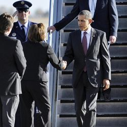 President Barack Obama, right, is greeted by Gov. Susana Martinez, center, and Roswell Mayor Del Jurney, left, during his arrival at Roswell International Air Center airport, March, 21, 2012, in Roswell, N.M. Interior Secretary Ken Salazar follows on the stairs.