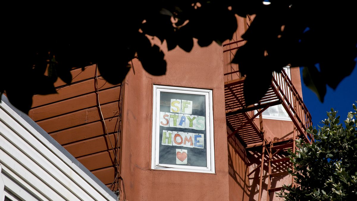"""A handwritten sign in the window of a red-painted apartment building surrounded by foliage reads """"SF Stays Home."""""""
