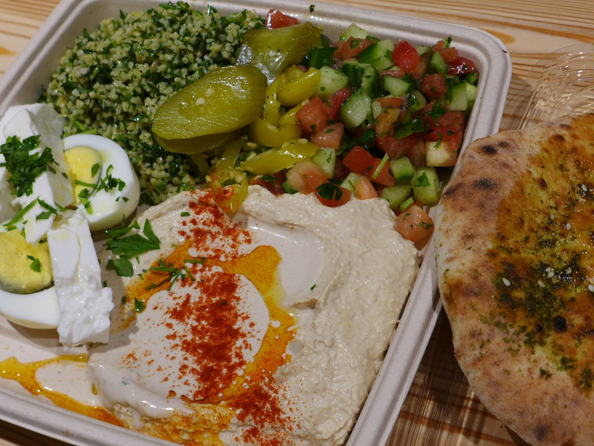 A plate with hummus with red powder and oil sprinkled on top, a cut up boiled egg next to it, along with greens and a piece of pita
