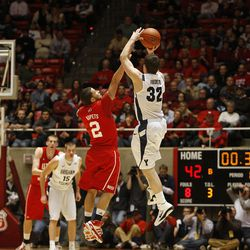 BYU's  Jimmer Fredette shoots over Chris Kupets to score at the end of the first half as the University of Utah and BYU play men's basketball Tuesday, Jan. 11, 2011, in Salt Lake City, Utah.