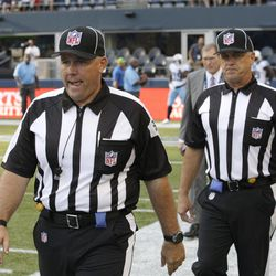 FILE - This Aug. 11, 2012 file photo shows replacement officials taking the field at the start of an NFL football preseason game between the Seattle Seahawks and the Tennessee Titans, in Seattle. The NFL will open the regular season with replacement officials. League executive Ray Anderson has told the 32 teams that with negotiations remaining at a standstill between the NFL and the officials' union. The replacements will be on the field beginning next Wednesday night, Sept. 5, 2012,  when the Cowboys visit the Giants to open the season.