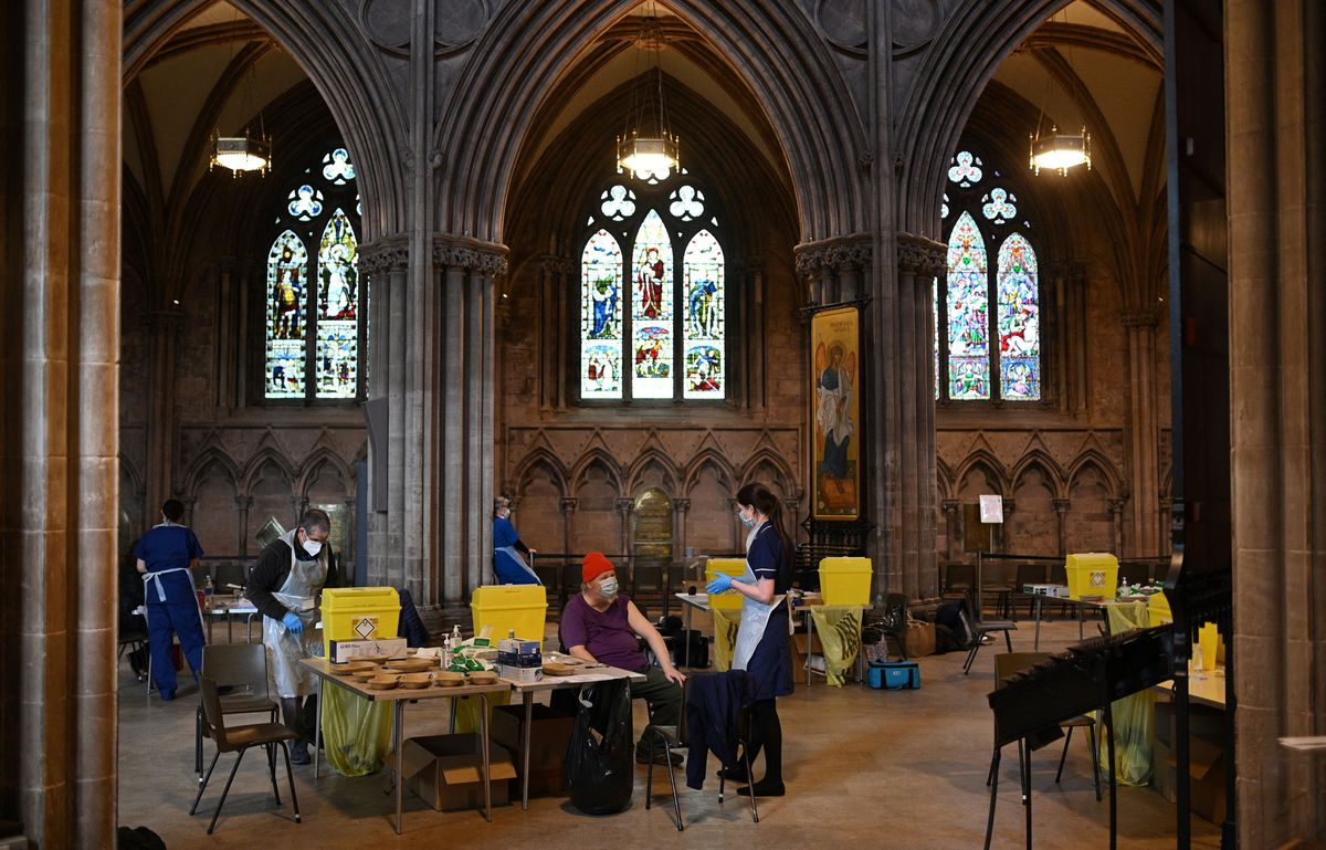 Members of the public receive a dose of the Oxford/AstraZeneca Covid-19 vaccine at Lichfield cathedral, which has been converted into a temporary vaccination centre, in Lichfield, central England on March 18, 2021.