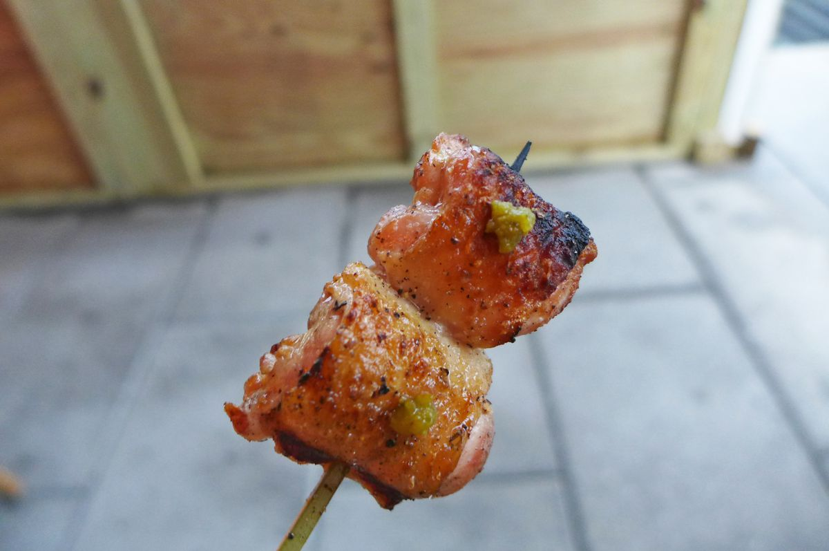 Two small squares of chicken on a wooden skewer.