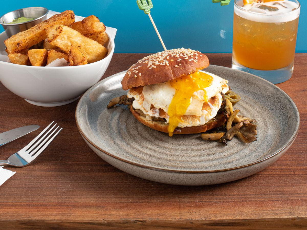 A breakfast sandwich with a gooey egg yolk on a bun is front and center, with an orange cocktail with a frothy top, and a white bowl of crispy potatoes in the background