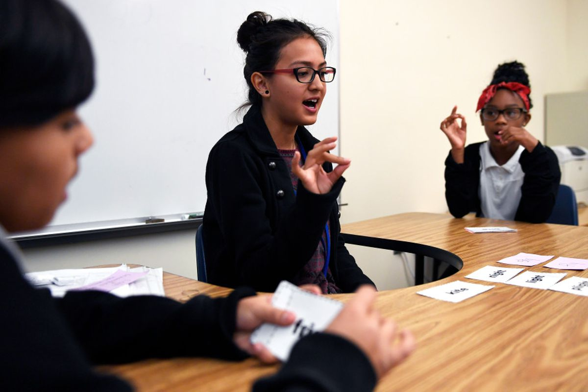Paraprofessional Sonia Guzman a student from the University of Northern Colorado's Urban Education Program tapping out the sounds of each word during a 2017 class at Elkhart Elementary school in Aurora. The program tries to get graduates from Denver and Aurora schools to come back to their old schools to be teachers.