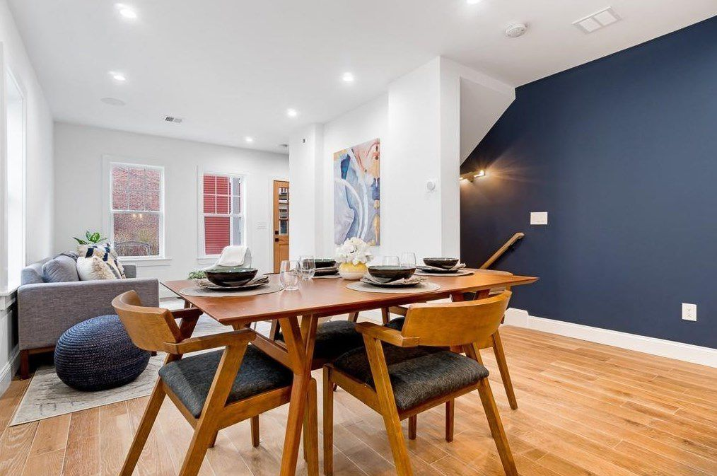 An open dining area with a table and chairs, and there's a stairwell leading down behind it.