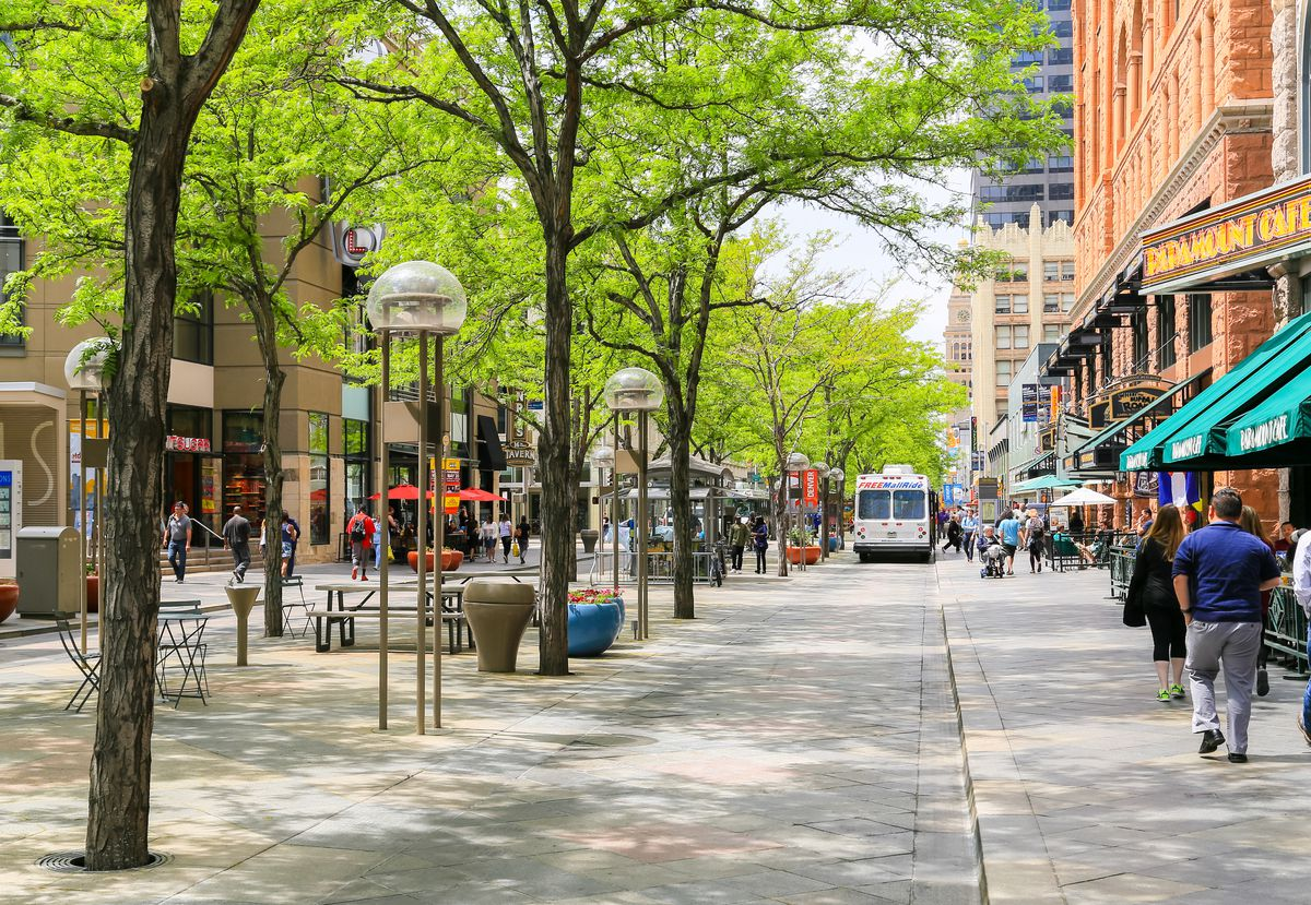 A pedestrian plaza in Denver. There are trees, lights, and benches. Stores and restaurants line the street. People are walking in the street.