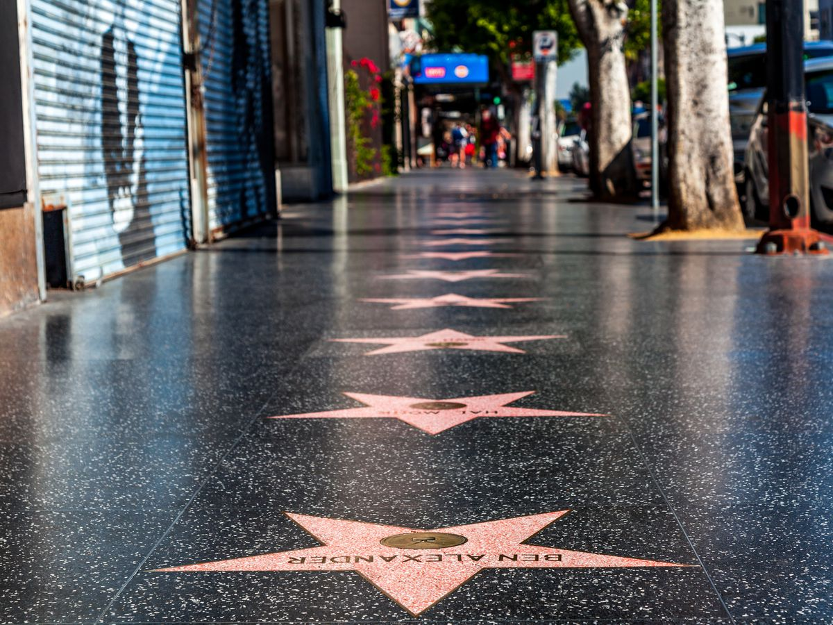 A charcoal-colored sidewalk with red-colored stars bearing the names of celebrities