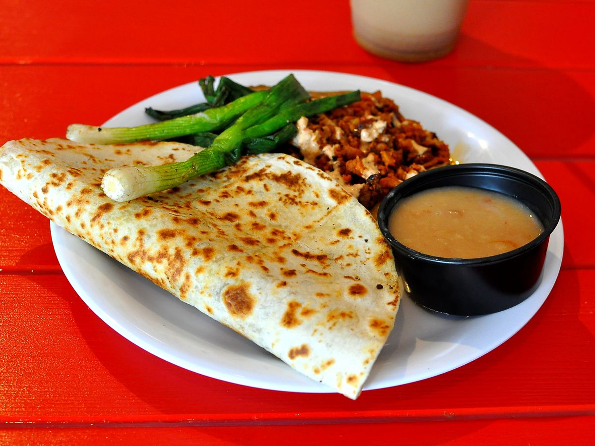 A quesadilla and vampiro on a bright red table at a Mexican restaurant.