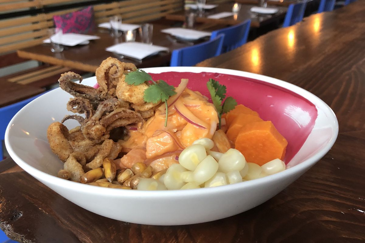 A bowl of ceviche in a light orange sauce sits in a bowl with crispy fried calamari and large Peruvian corn kernels.