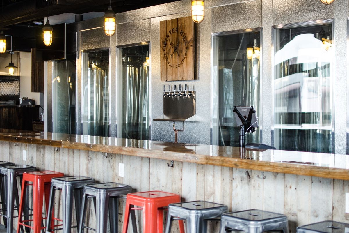 Interior shot of the bar at a brewery. A glossy wooden bar has red and silver metal stools.