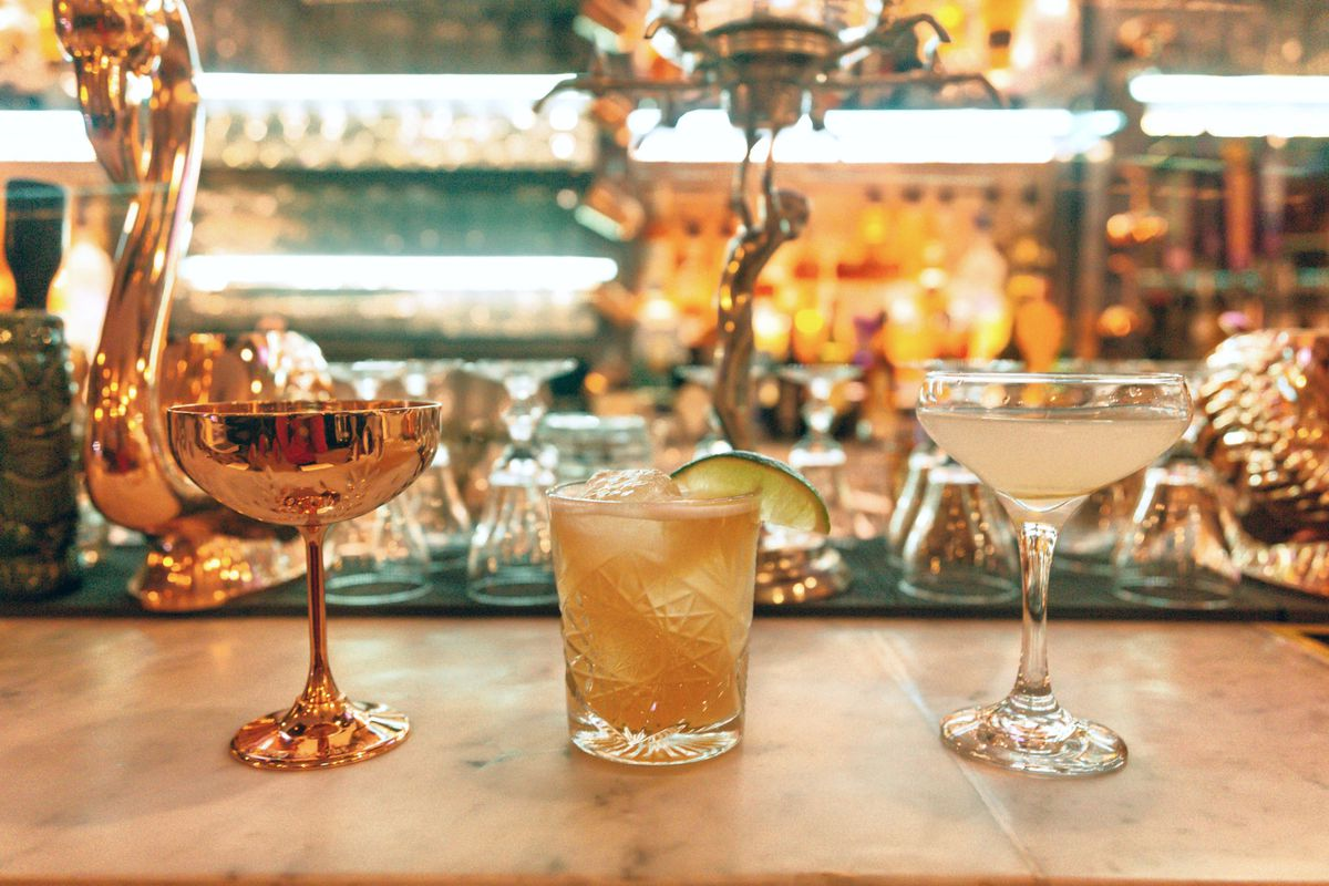 A close-up photo of three cocktails placed on a bar with a backlit wall of bottles of liquor in the background