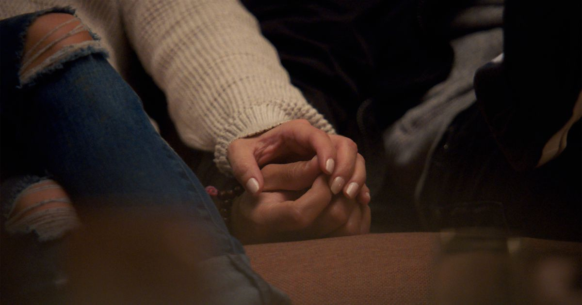 Two people hold hands