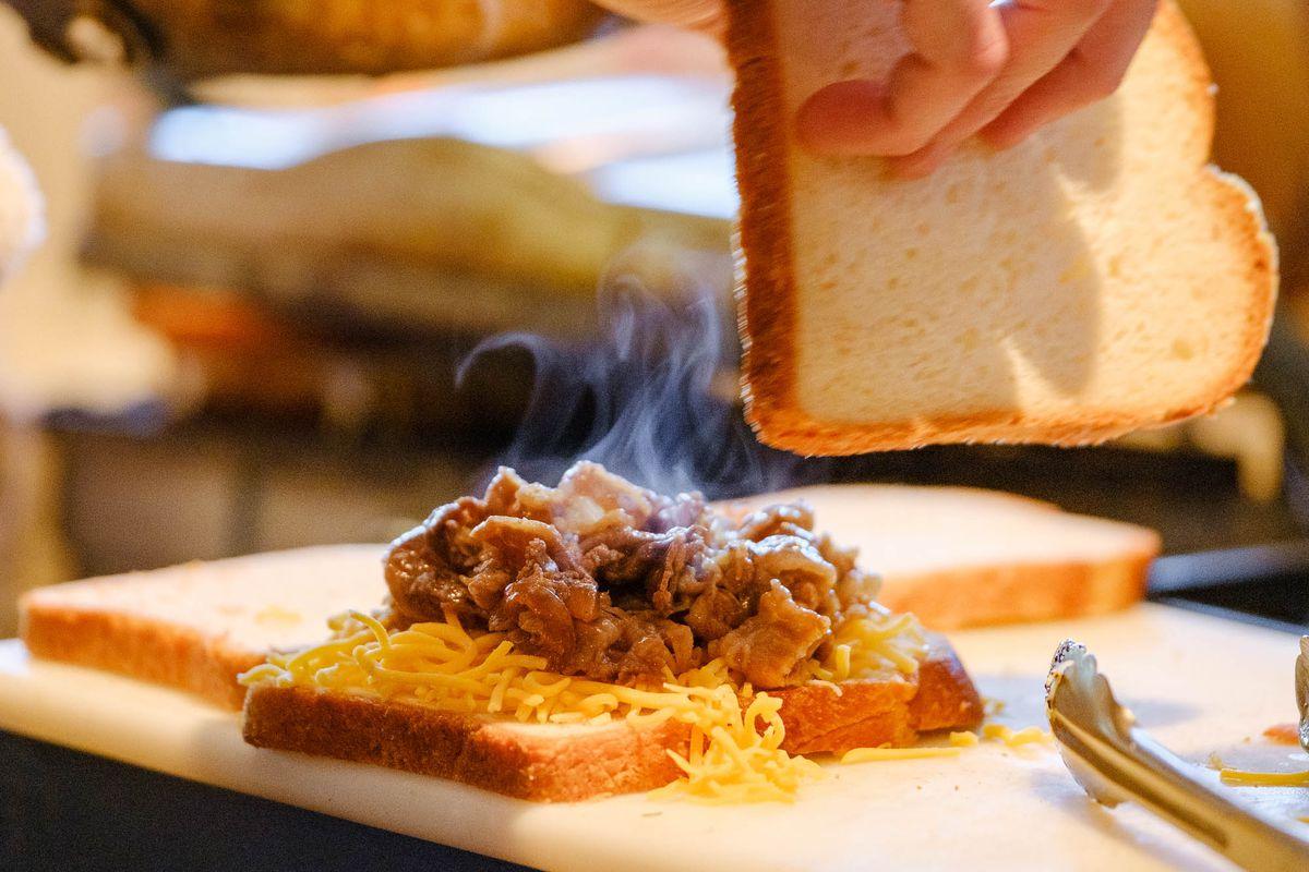 An open faced steaming sandwich.