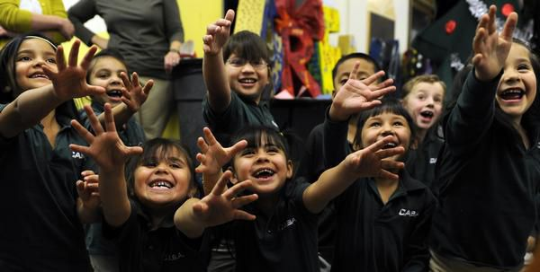 Kindergarten students at Cole Arts & Science Academy wait to receive holiday gifts from a local philanthropist in 2010.