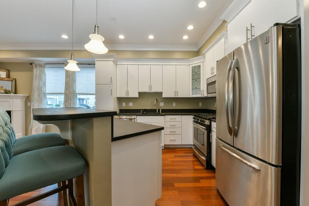 A kitchen with a wide opening between two counters.