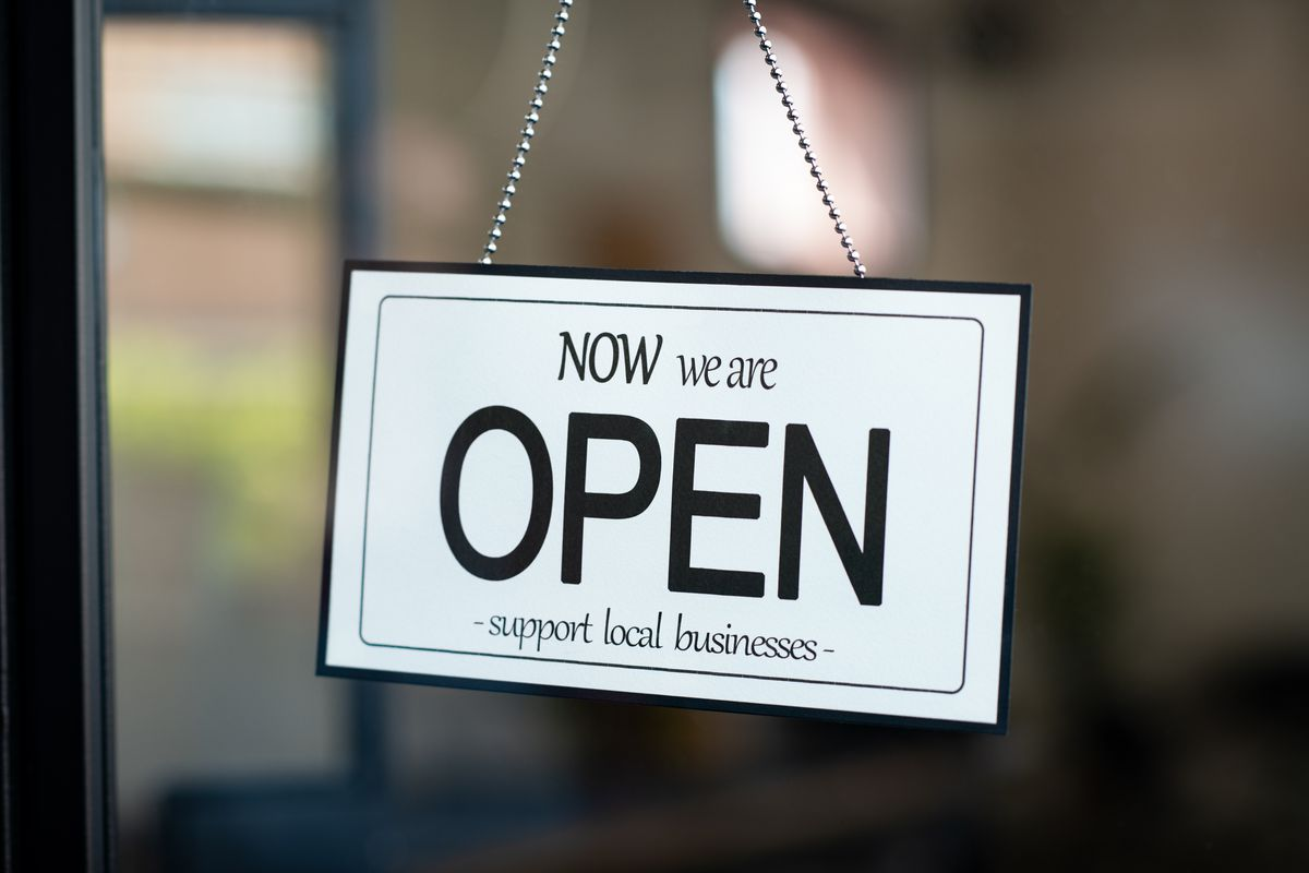 """A sign outside a restaurant reads, """"Now, We're Open, Support Local Businesses"""""""