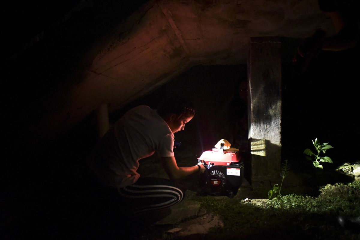FILE - In this Dec. 21, 2017 filw photo, barrio Patron resident Karina Santiago Gonzalez works on a small power plant in Morovis, Puerto Rico. Puerto Rico authorities said on Friday Dec. 29, that nearly half of power customers in the U.S. territory still