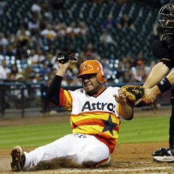 Houston Astros' Jose Altuve, left, is tagged out by Pittsburgh Pirates catcher Rod Barajas, right, while trying to score during the third inning of a baseball game, Sunday, Sept. 23, 2012, in Houston.