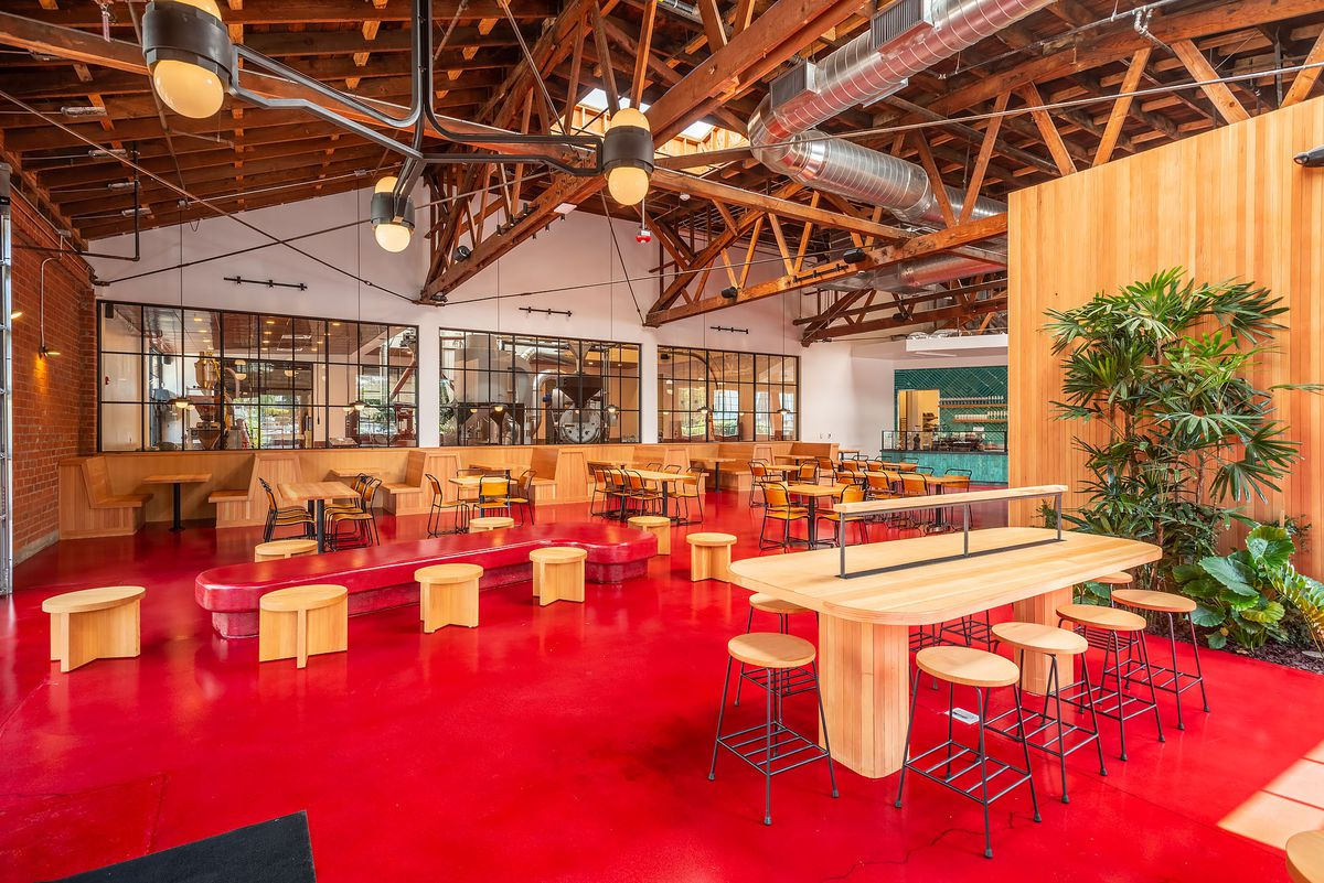 A corner view of a new cafe with red floor and wooden stools.