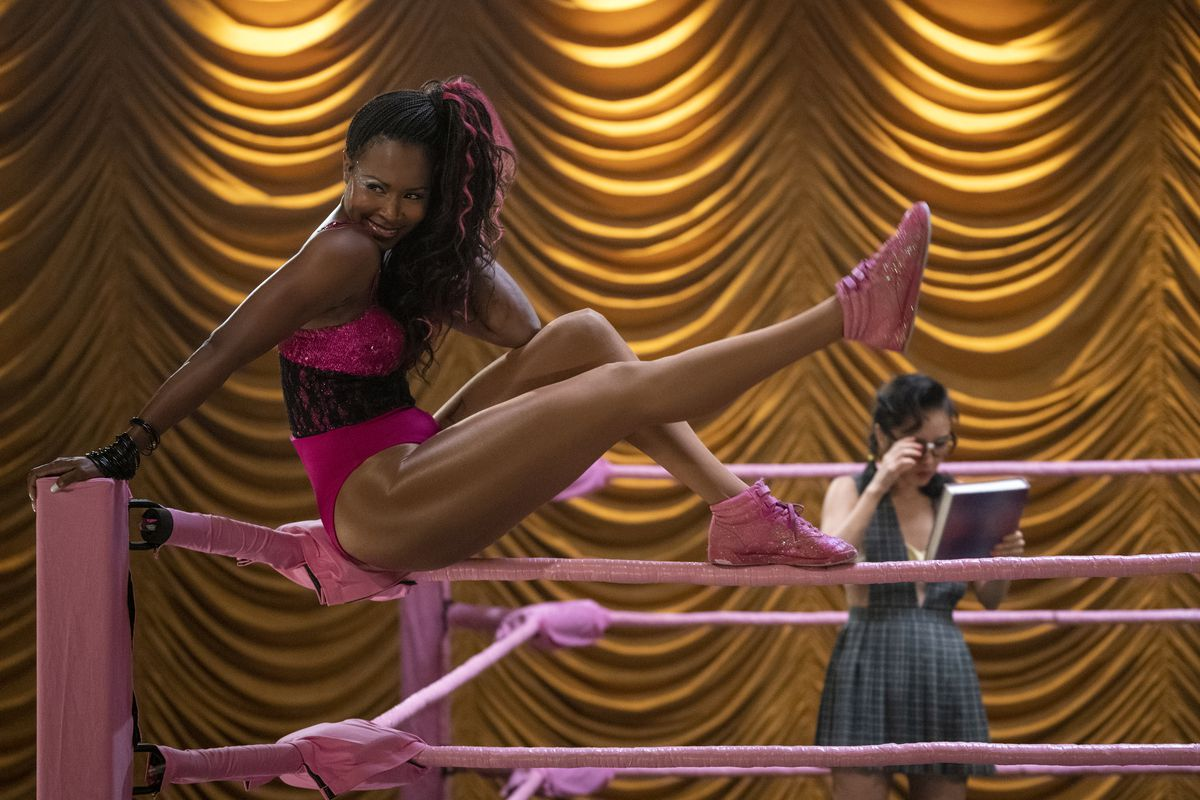Cherry Bang in pink sneakers, a pink leotard, and pink highlights in her hair perches on the corner of a wrestling ring, which is also pink. She is extending one leg and smiling playfully. There's a golden curtain behind her and a woman in a green dress c