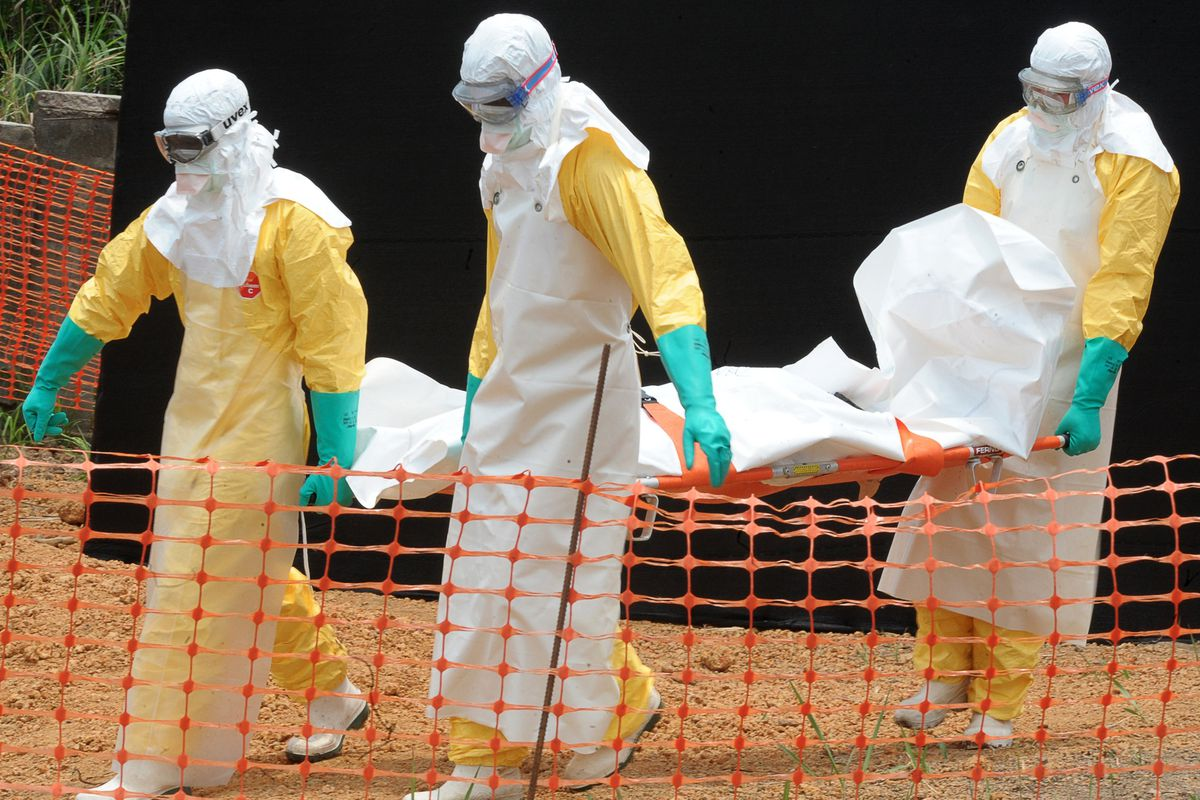 Staff of medical aid organization Doctors without Borders carry the body of a person killed by viral haemorrhagic fever, at a center for victims of the Ebola virus in Guinea.