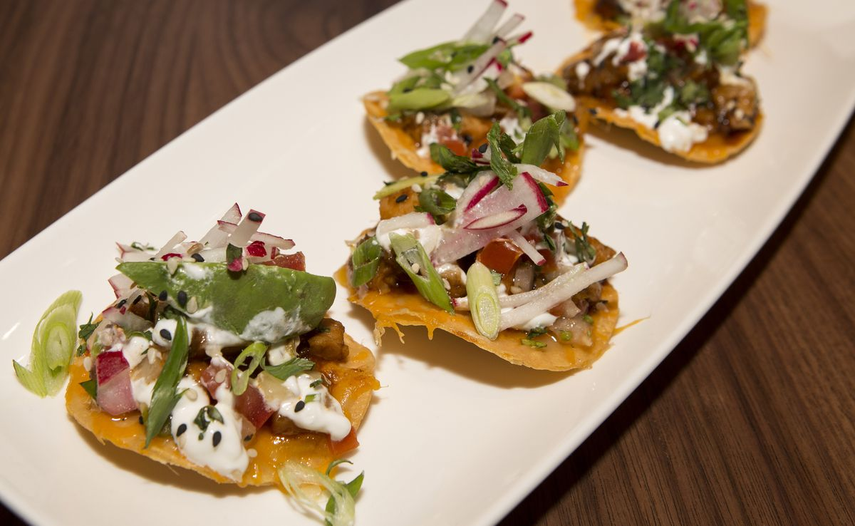 Five small pork belly tostadas on a white plate