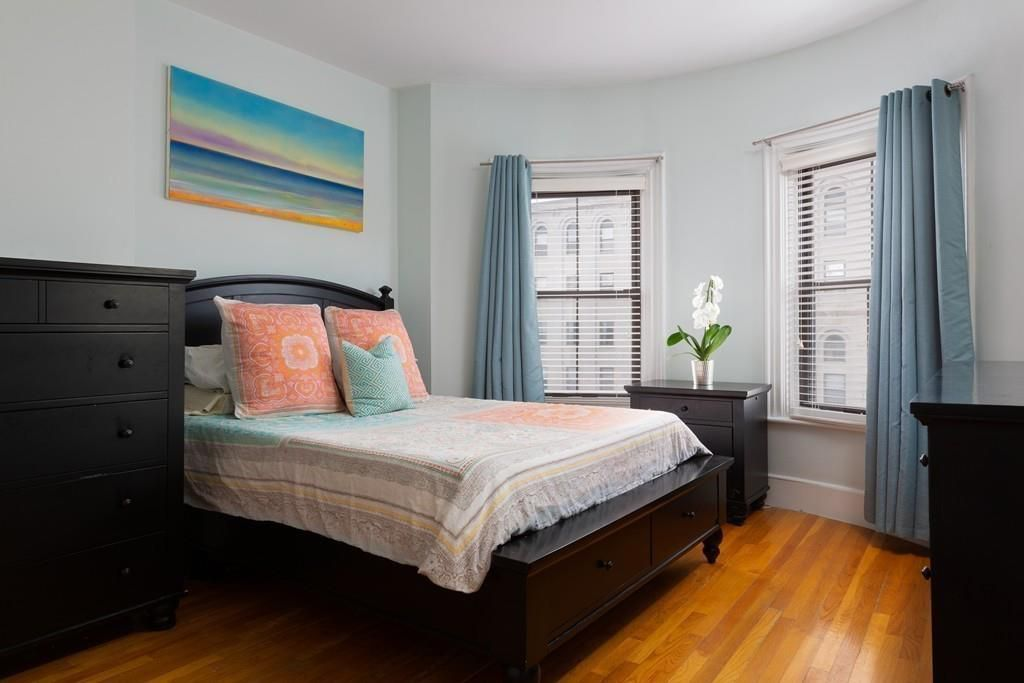 A bedroom with a bed and two windows bowing out.