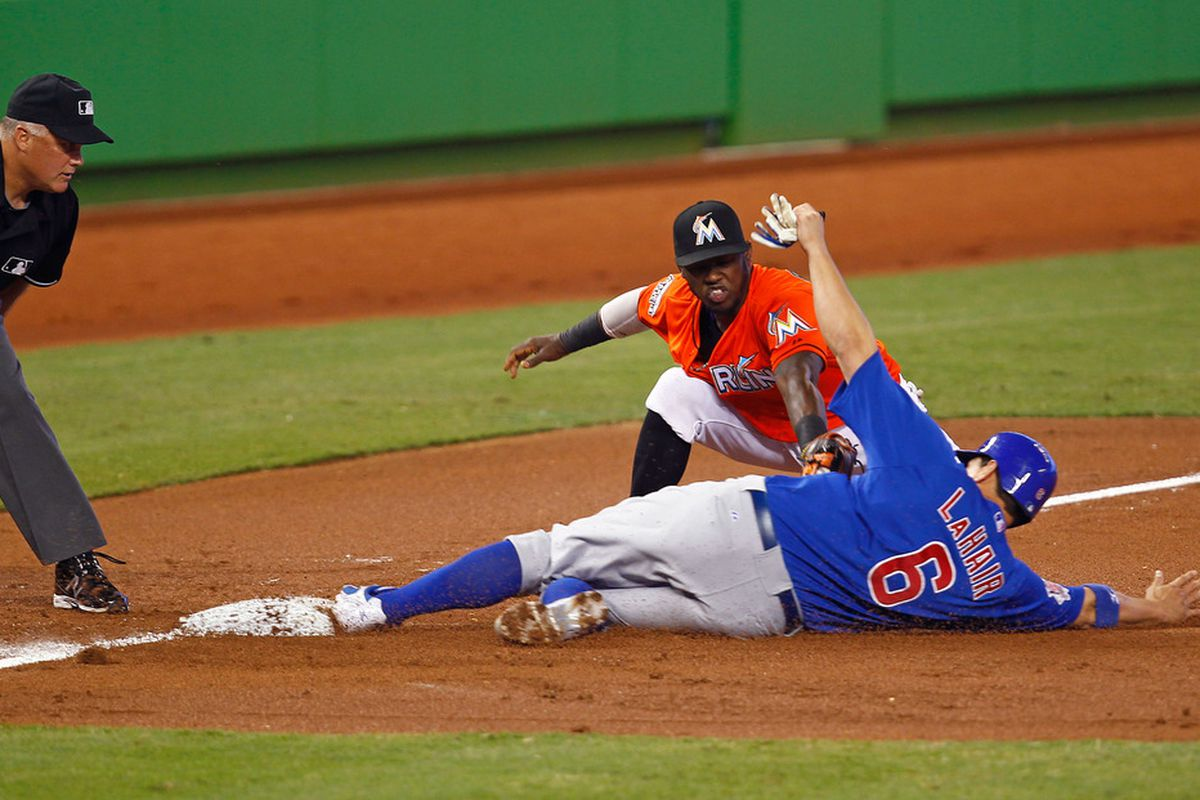 MIAMI, FL - APRIL 19:  Bryan LaHair #6 of the Chicago Cubs slides safely into third under the tag of Jose Reyes #7 of the Miami Marlins during a game at Marlins Park on April 19, 2012 in Miami, Florida.  (Photo by Sarah Glenn/Getty Images)