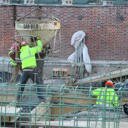 Concrete being poured in the left-field bleachers on Waveland