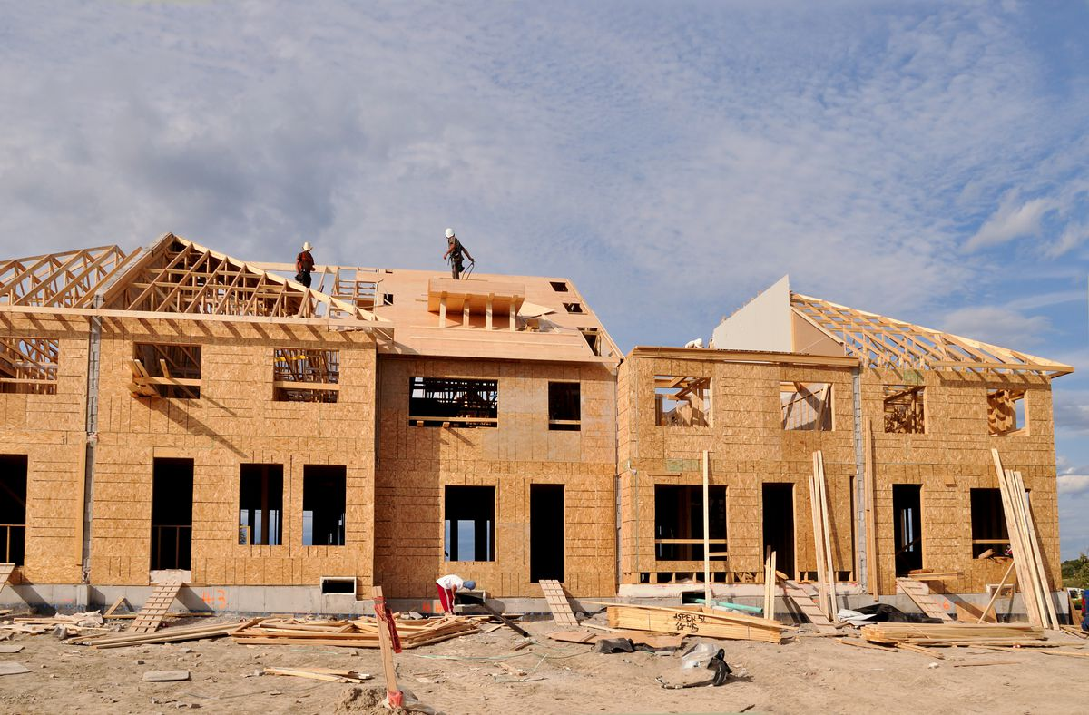 The wooden frames of a series of townhomes under construction.